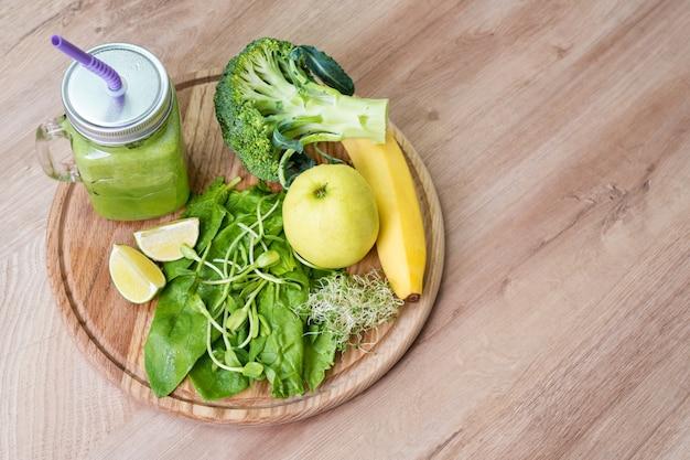新鮮な緑の野菜と緑の瓶にスムージー。デトックス、ダイエットや健康食品のコンセプトです。ブロッコリー、ほうれん草、microgreens、ライム、木製の背景にバナナの食事の飲み物の石工の瓶。上面図。
