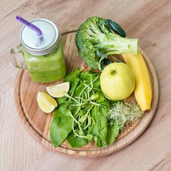 Свежие зеленые овощи и зеленый коктейль в банке. детокс, диета или концепция здорового питания. кувшин мейсон диетического напитка с брокколи, шпинат, microgreens, лайм и банан на деревянный стол. вид сверху.