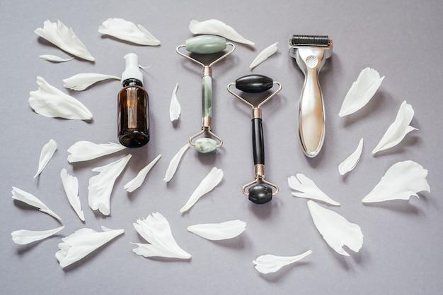 마이크로니들링 더마 롤러, 제이드 구아샤 마사지 롤러, 배경에 흰색 모란 꽃잎이 있는 혈청 병, 홈 마이크로니들링 및 스킨케어