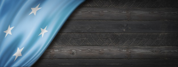 검은 나무 벽에 미크로네시아 플래그입니다. 수평 파노라마 배너.
