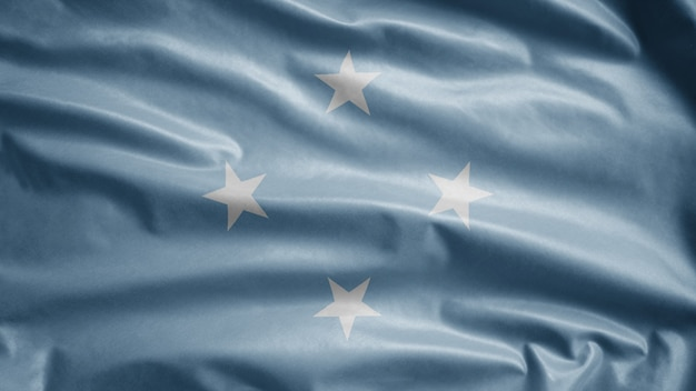 Micronesian flag waving on wind. close up of micronesia banner blowing, soft and smooth silk