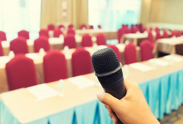 Microphone over the abstract blurred photo of conference hall or seminar room