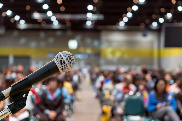 Microphone over the abstract blurred photo of conference hall