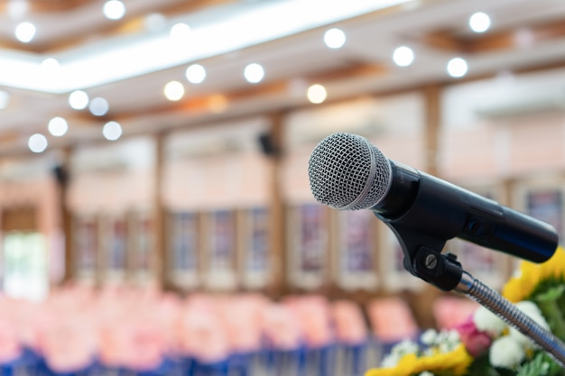 Microphone on abstract blurred of speech in seminar room or speaking conference hall