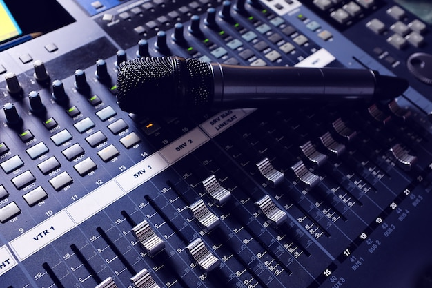 Microphone, amplifying equipment, studio audio mixer knobs and faders. sound engineer equipment. acoustic mixing of music, selective focus. the photo is covered in grit and noise.