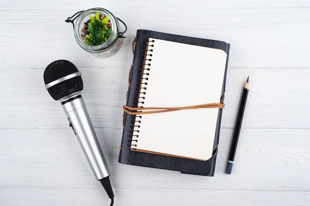 Микрофон и пустая открытая записная книжка на белом деревянном