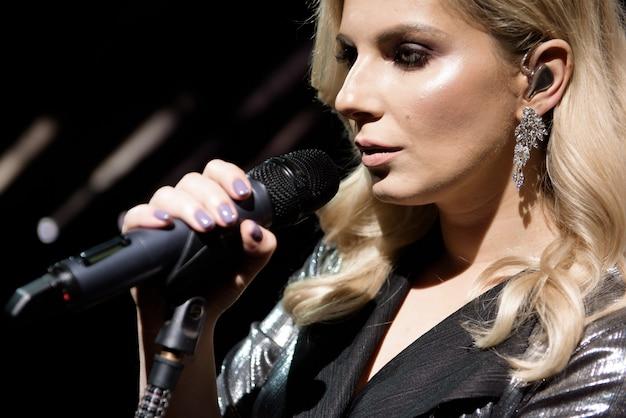 Микрофон и певица крупным планом. женщина поет в микрофон, держа микрофон двумя руками.