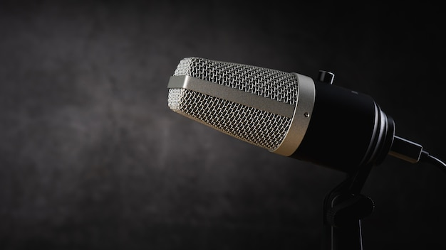 Microphone for audio record or podcast concept, single microphone on dark shadow background with copy space