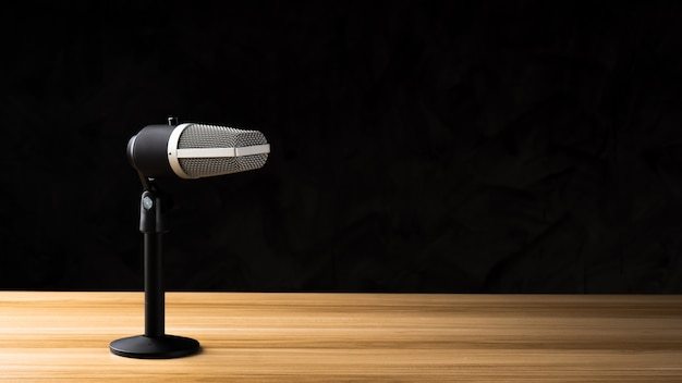 Microphone for audio record or podcast concept, single microphone on dark shadow background  on wood table with copy space