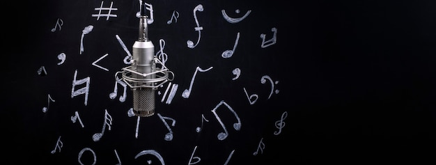 Microphone on the background of the board for chalk with painted notes, panoramic image with space for text, music time concept