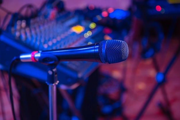 Microphone on the blurred background of the audio mixer of the musician.