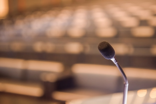 Microphone over the blurred conference room concept.