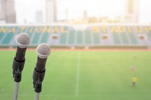 Microphone for commentator with sport football field stadium with space for text