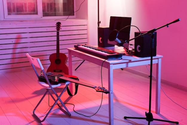 Гитары микрофона, компьютера и музыкального оборудования и фон фортепиано. концепция домашней студии звукозаписи.