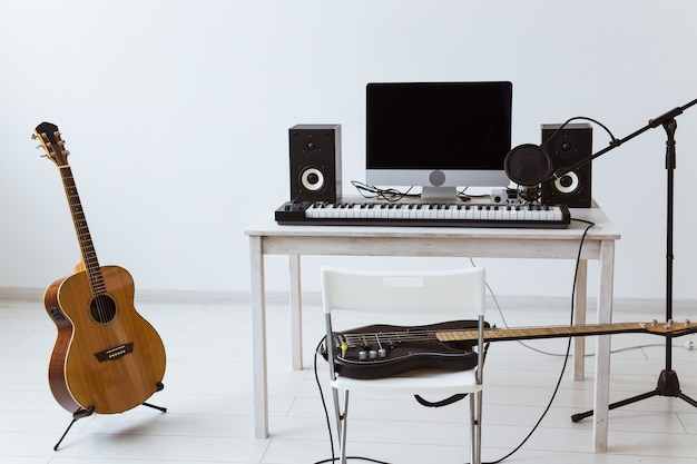 Microphone, computer and musical equipment guitars and piano background. home recording studio