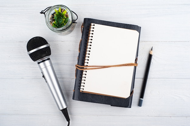 Microphone and empty open note book on white wooden