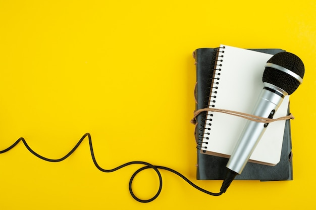 Microphone and empty open note book on yellow paper
