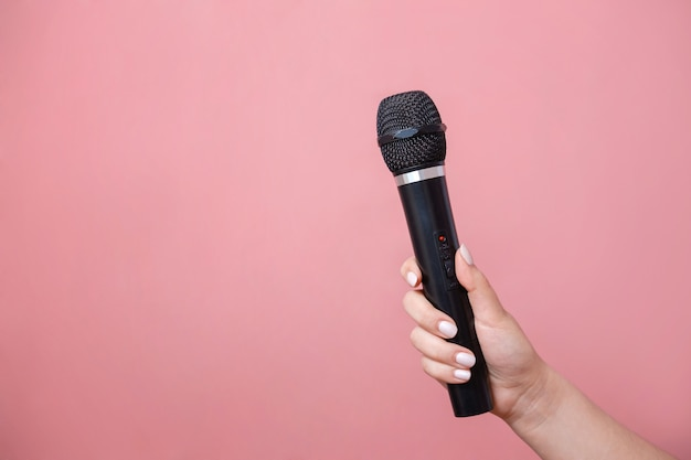 Microphone in female hand on pink wall stock photo
