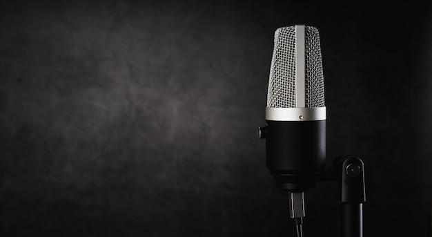Микрофон для аудиозаписи или концепции подкаста, один микрофон на темном теневом фоне с копией пространства
