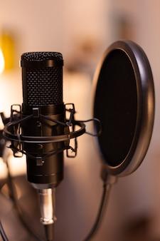 レコーディングの準備ができているホームスタジオの有名なインフルエンサーのポッドキャスト用のマイク。プロダクションマイクを使用してソーシャルメディアコンテンツをログに記録します。デジタルウェブインターネットストリーミングステーション