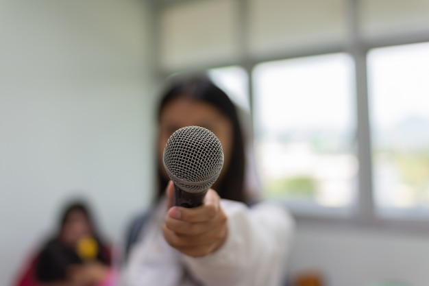 Microphone in a hand of a woman.
