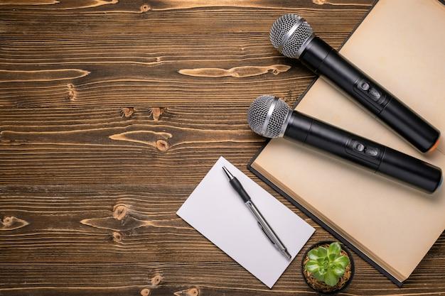 Примечание микрофона, наушников, книги и бумаги на коричневой деревянной доске. изучение понятия речи
