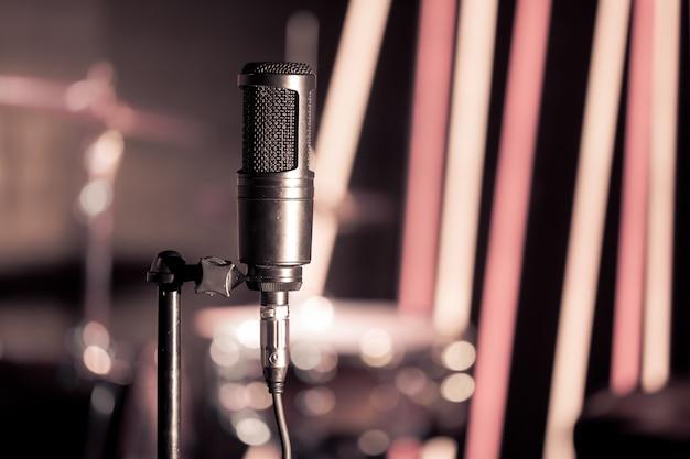 Микрофон в студии звукозаписи или концертном зале крупным планом, с ударной установкой