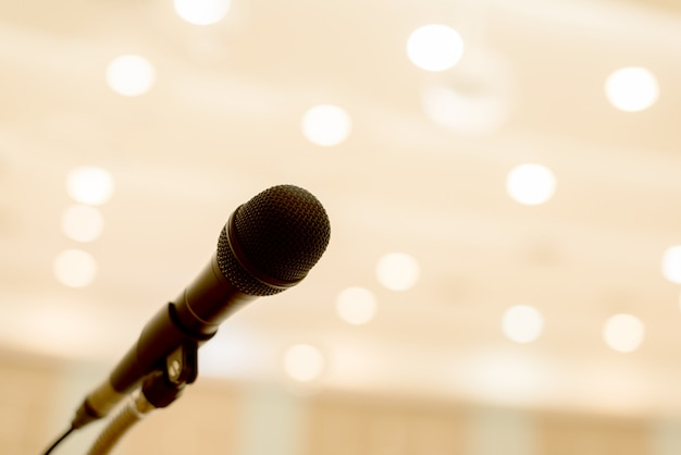 Microphone is located on the podium in a conference or seminar room with light of bokeh