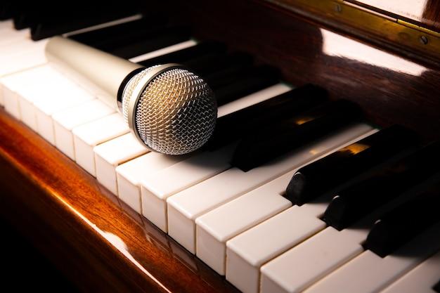ピアノのキーボードの上に横たわっているマイク。自宅での自由時間の活動。カラオケ趣味。音楽を作る。