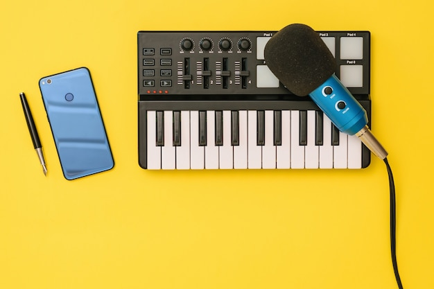 Microphone, mixer, smartphone and pen on yellow surface