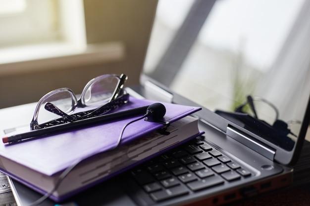 ノートパソコンのマイク、ノートブック、メガネ、黒鉛筆。ポッドキャストの計画