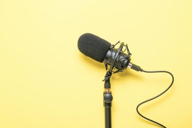 노란색 표면에 연결된 와이어가있는 스탠드의 마이크. 녹음 장비.
