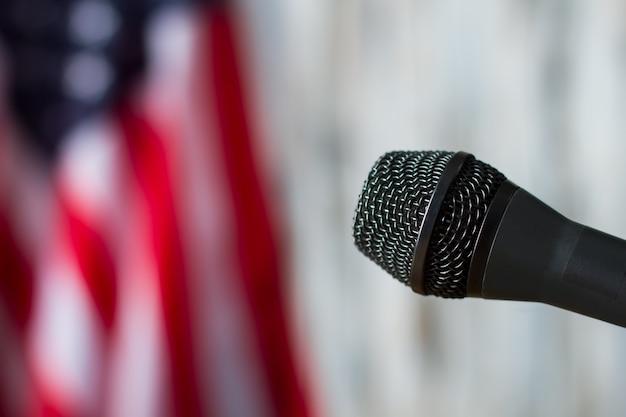 ぼやけた旗の背景にマイク。アメリカの国旗の横にあるマイク。機器はスピーチの準備ができています。国のためのニュース。