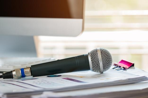 Микрофон на бумажном документе на семинаре с графическим интерфейсом. спикер коммуникационных технологий