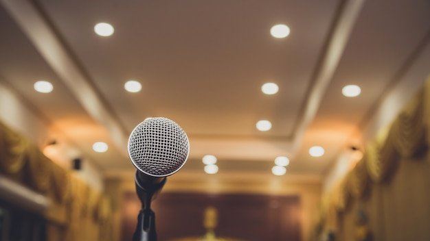 Microphone onbstract blurred in seminar room or speaking conference hall, event