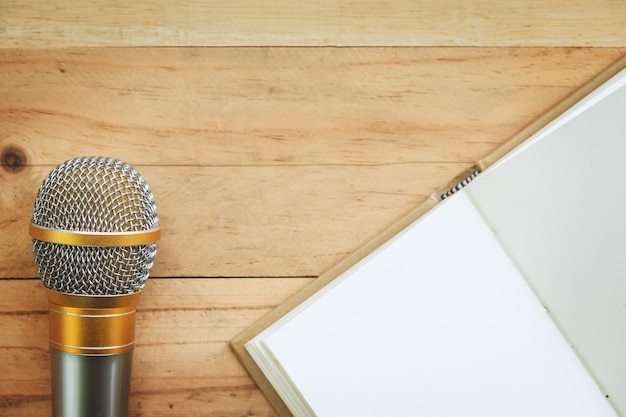Microphone and opened notebook on wooden background