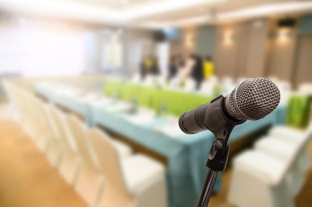 ぼやけたビジネスフォーラム会議または会議トレーニング学習コーチングルームのコンセプト、背景をぼかした写真の上のマイク。
