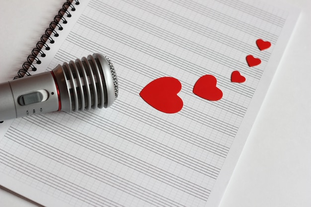Microphone and paper red hearts are located on a clean music notebook. the concept of music and love.