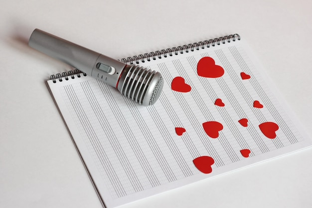 Microphone and paper red hearts are located on a clean music notebook.
