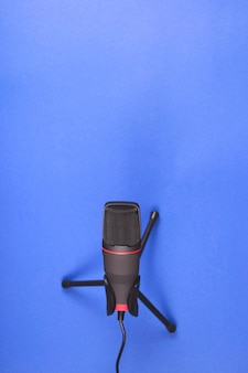 Microphone for recording sound and podcasts on blue.