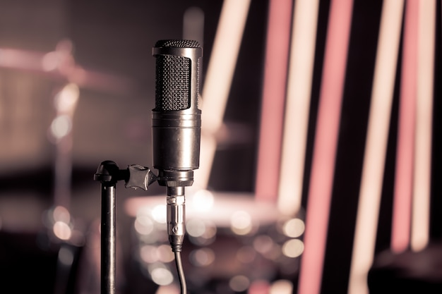 Microphone in recording studio or concert hall close-up, with drum set