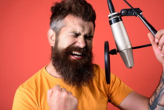Микрофон. шоу-бизнес. звукозаписывающая студия. эмоциональный бородатый мужчина поет в микрофон. музыка. певец с микрофоном. передатчик. пение. концепция музыки и досуга.