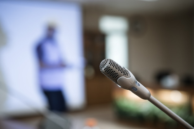 Microphone for speech on abstract blurred conference hall