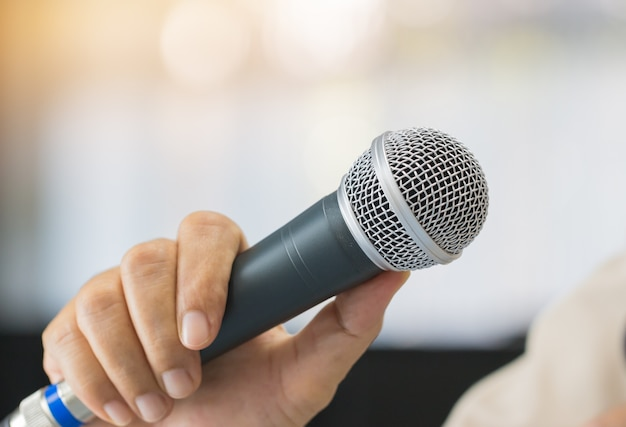 Microphone of speech in seminar room or speaking conference hall light bokeh background.