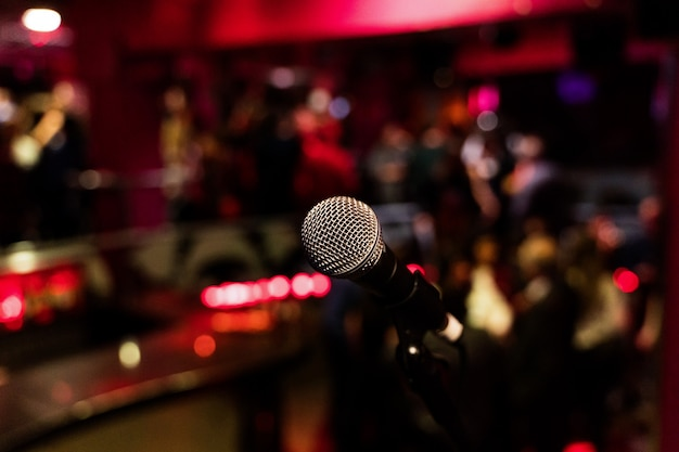 Microphone on a stand up comedy stage with colorful bokeh