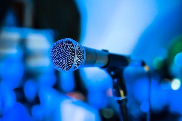 Микрофон стоит на сцене в ночном клубе. яркий клубный свет светит на микрофон