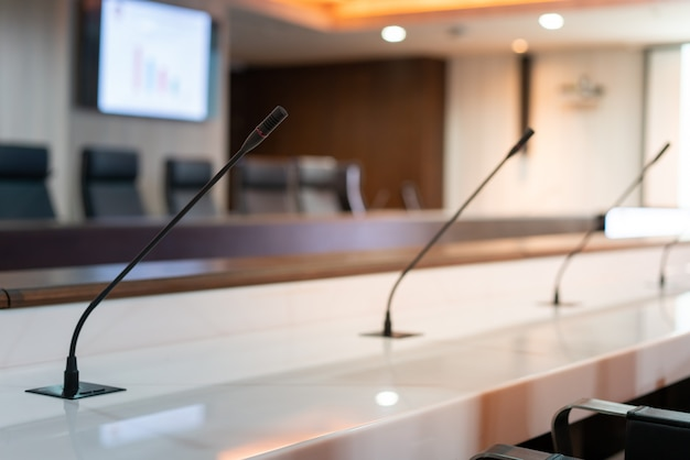 Microphone on table in meeting room photo of conference hall or seminar room background (select focus)