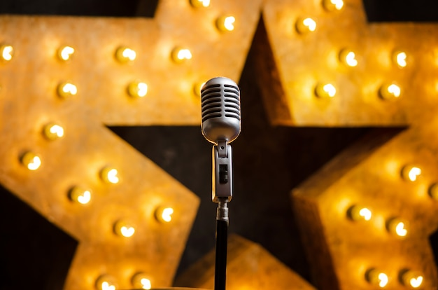 Microphone on theater or karaoke stage, golden luminous star on background