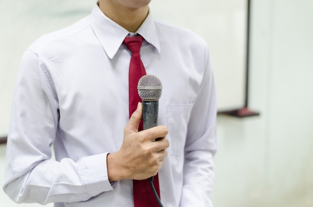 Microphone with background of a man in tie standing before the white board