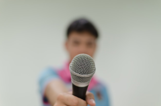Microphone with blurred background of a man holding a mic